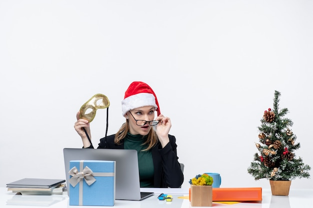 Curiosa giovane donna con cappello di babbo natale occhiali e maschera seduto a un tavolo con un albero di natale e un regalo su di esso in ufficio su sfondo bianco