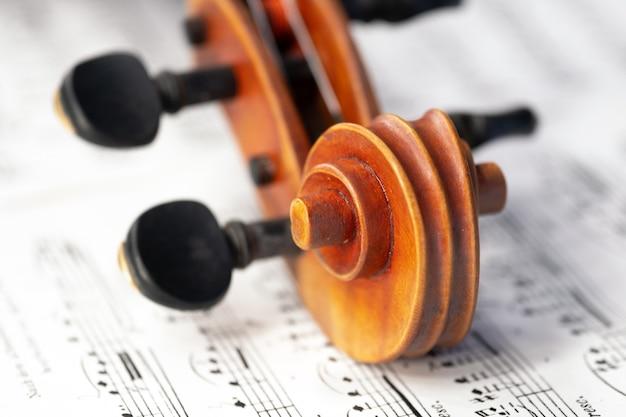 楽譜の上にペグが横たわっているバイオリンのカールがクローズアップ