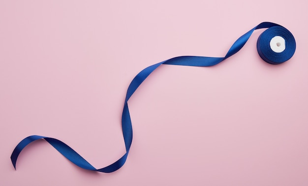 Curled blue satin ribbon on pink surface