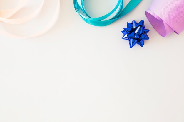 Curled colorful ribbon and blue stain bow on white background