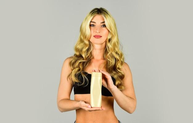 곱슬머리 관리. 컨디셔너를 선택 하는 곱슬 머리를 가진 소녀입니다. 곱슬 금발 머리에 영양 오일을 바르고 병을 들고 젊은 여자. 컨셉 미용실 스파 살롱. 화장품 케어 제품을 적용합니다.