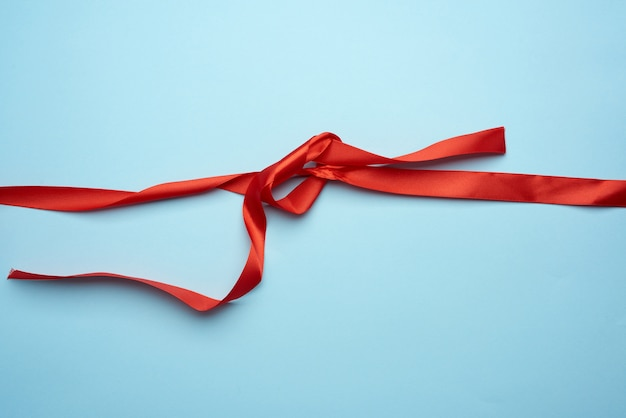 Curled red silk ribbon on blue background