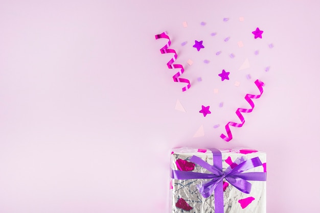 Curled streamers, star shape and confetti over the silver gift box against pink background