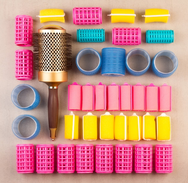 Curlers for hair of different colors and comb top view close-up