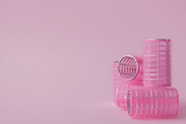Curlers hair plastic on a pink space with copy space