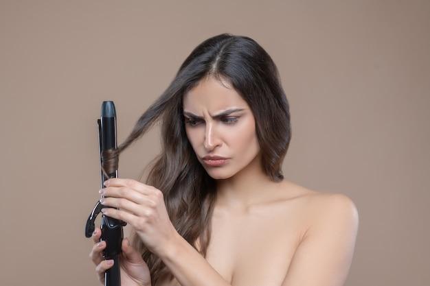 カーリングカール。黒のヘアアイロンで彼女のカールを巻く裸の肩を持つ深刻な若い黒髪の女性