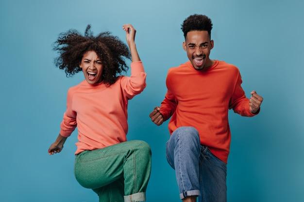 青い壁にジャンプするオレンジ色のスウェットシャツの巻き毛のアフリカの男と女