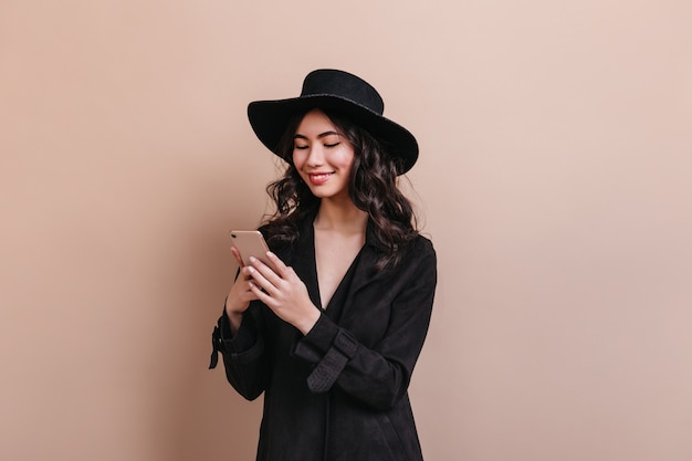 Curly asian woman holding smartphone. laughing korean woman in coat posing with gadget.