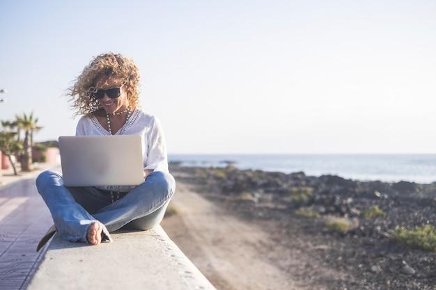 곱슬 매력적인 젊은 백인 여자는 해변 근처 야외에서 노트북에서 작동-라이프 스타일을 즐기는 무료 사람들을위한 인터넷 사방과 프리랜서 디지털 유목민 개념