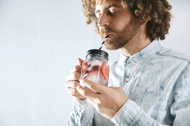 Curly bearded man in shirt enjoys fresh home made strawberry with ice sparkling lemonade through striped drinking straw from rustic transparent jar in hands