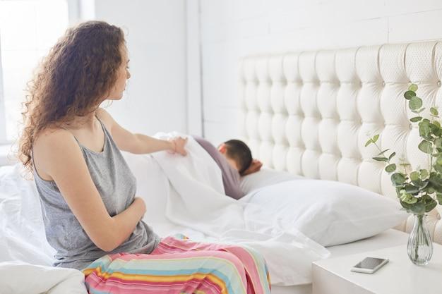パジャマの巻き毛の美しい女性はベッドの側に座って、カジュアルなパジャマに身を包んだ、夫を目覚めさせようとする、関係に問題がある、居心地の良い寝室でポーズを取る、家族や睡眠の概念