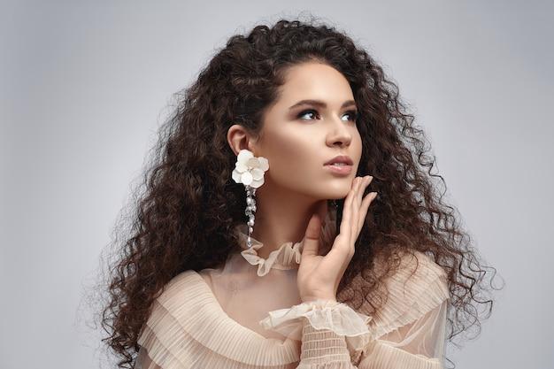 Curly beauty brunette with earrings.