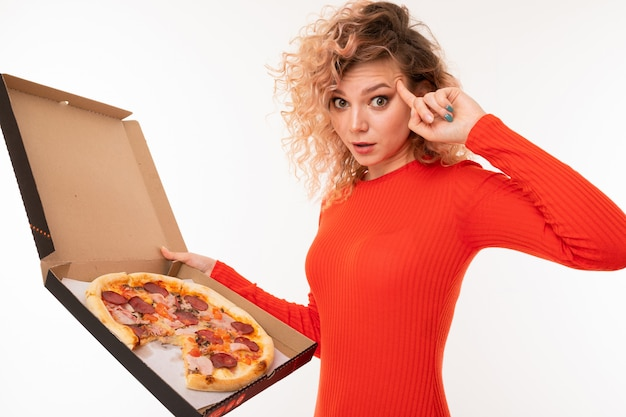 Curly blond girl shows thinking holding a pizza box in her hand on white