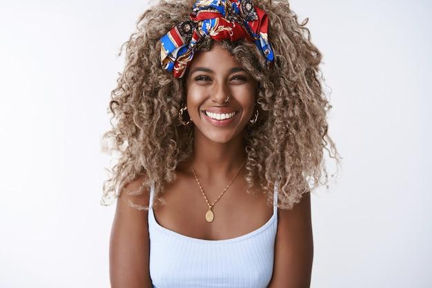 세련된 옷을 입은 곱슬곱슬한 금발 여성, 피어싱 웃는 이빨, 진지한 행복한 표정, 열광적으로 웃고, 멋진 파티를 즐기세요