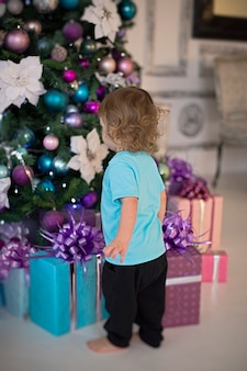 A curly blonde boy in a mintcolored tshirt looks at the gifts under the christmas tree