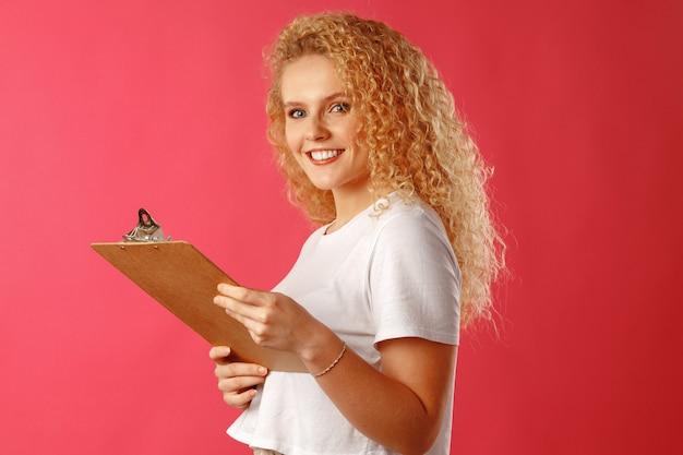 Кудрявая блондинка бизнесвумен, держа в руках буфер обмена крупным планом