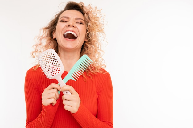 Curly blonde girl holds hair combs in her hands on a white background with copyspace
