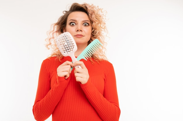Curly blonde girl holds hair combs in her hands on a white wall with copyspace.