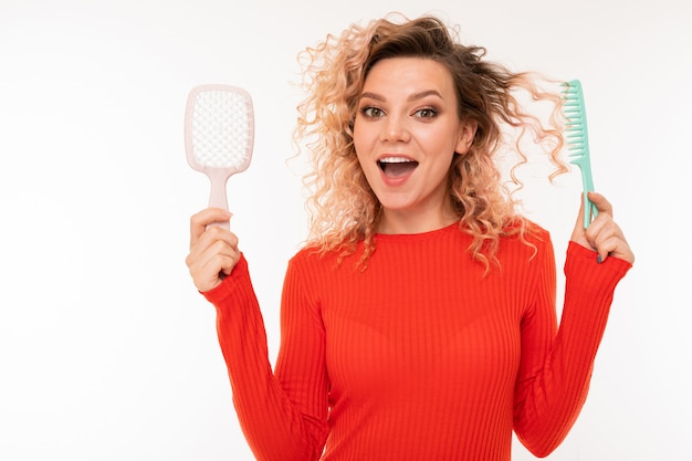 Curly blonde girl holds hair combs in her hands on white