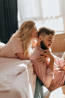 Curly blonde girl kisses her boyfriend in striped shirt sitting on floor in bright bedroom.
