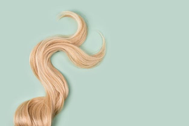 민트 바탕에 곱슬 금발 머리입니다. 아름다운 건강한 긴 금발 머리 자물쇠, 이발, 헤어 스타일. 염색 머리 또는 착색, 머리 확장, 치료, 치료 개념. 텍스트를위한 공간을 복사합니다.