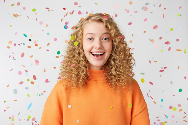 Curly blonde in orange sweater enjoying life moment, under confetti rain