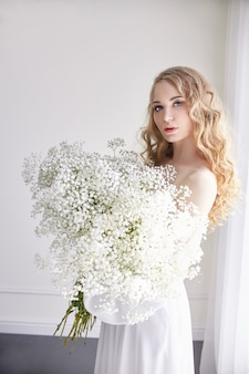 カーリーブロンドのロマンティックな表情、美しい瞳。手には白いワイルドフラワー。女の子の白い光のドレスと巻き髪