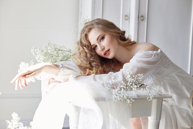Curly blonde romantic look, beautiful eyes. white