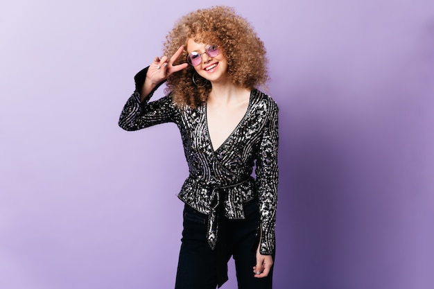 Curly blonde in shiny blouse, black pants and lilac glasses smiles and shows peace sign on purple space.