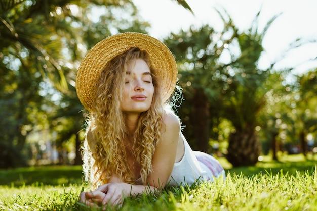 彼女の目を覆っている巻き毛の金髪の肩をすくめることは公園の草の上にあります