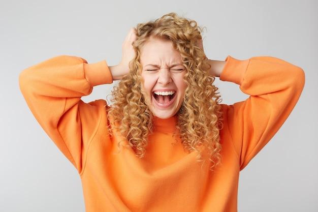 Кудрявая блондинка стоит с закрытыми глазами с широко открытым ртом, кричит, хватаясь за голову, не выдерживает напряжения