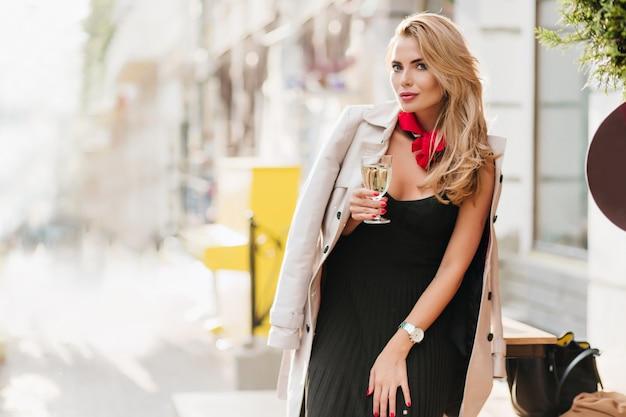 Donna bionda riccia in vestito pieghettato nero che celebra qualcosa con champagne. ritratto all'aperto della ragazza bionda felice che tiene un bicchiere di vino.