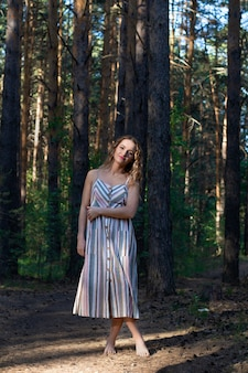 Curly blonde woman in a dress walks in a pine forest