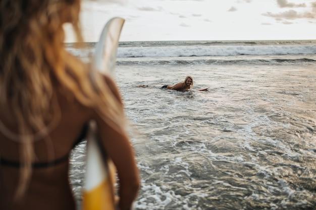 巻き毛のブロンドの女性はサーフィンに行きます