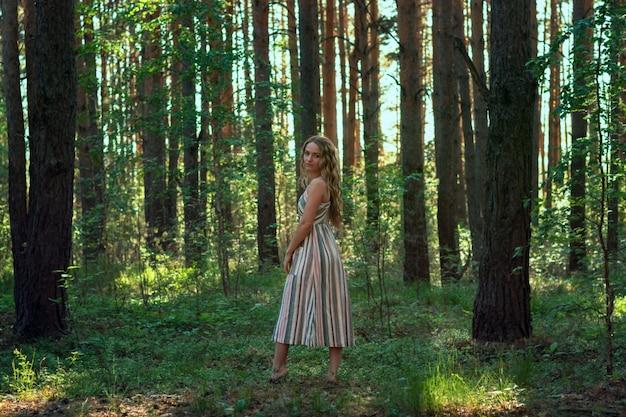 Кудрявая блондинка в платье гуляет в сосновом лесу