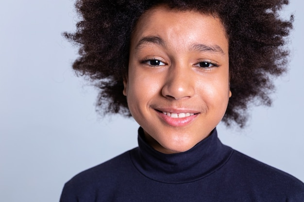 Curly boy behaving. cute smiling young boy with black eyes posing during photoshoot while lightly smiling
