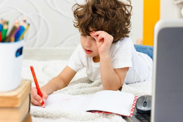 Кудрявый мальчик занимается компьютером. школьник удивленно хватается за голову. понятие о трудностях домашнего обучения, дистанционного обучения.
