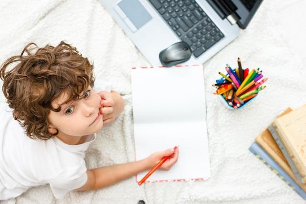 Кудрявый мальчик занимается компьютером. школьник смотрит вверх. понятие о трудностях домашнего обучения, дистанционного обучения