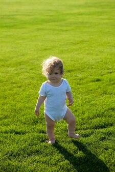 Кудрявый мальчик на зеленой траве