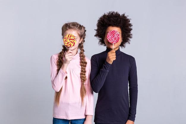 カーリーボーイ。彼らの顔の前に棒で大きなカラフルなキャンディーを運ぶ細い珍しい子供たち