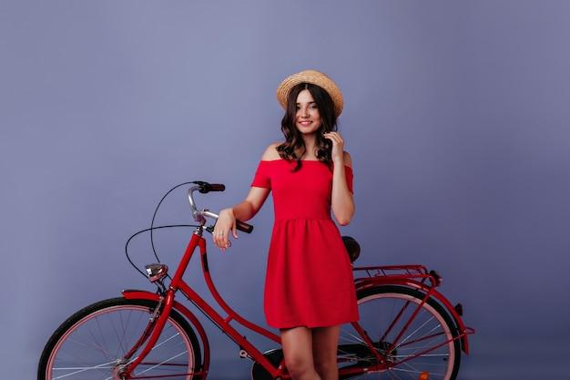 그녀의 자전거 앞에 서있는 모자에 곱슬 갈색 머리 소녀. 보라색 벽에 포즈를 취하는 자전거와 함께 즐거운 백인 여자의 실내 샷.