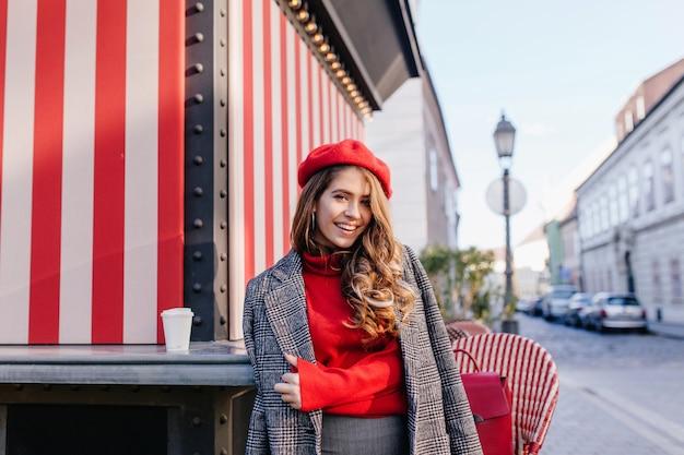美しいヨーロッパの通りに灰色のコートでポーズをとって誠実な笑顔と巻き毛の茶色の髪の少女
