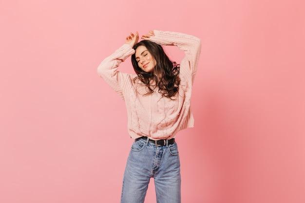 ピンクの背景に踊る巻き毛のブルネット。暖かいセーターとママのジーンズで素晴らしい気分の女の子の肖像画。