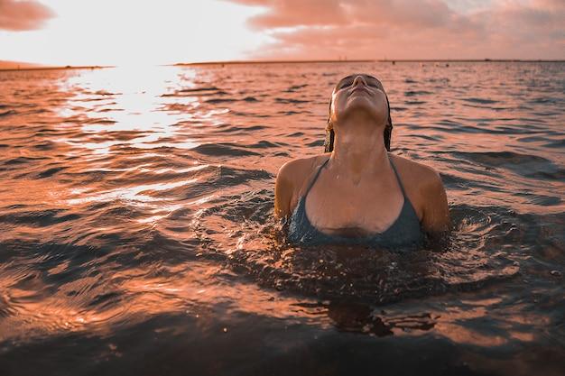 曇りの夕焼け空の下で海でポーズをとる巻き毛のブルネットの女性