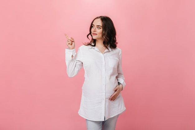 孤立した上のテキストの場所を指している白いシャツの巻き毛のブルネットの妊婦。デニムパンツの幸せな女の子は、ピンクの背景に笑顔とポーズをとる。