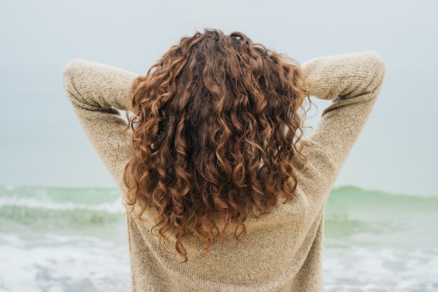 Curly brunette in a sweater on the coast faces the sea and straightens hair