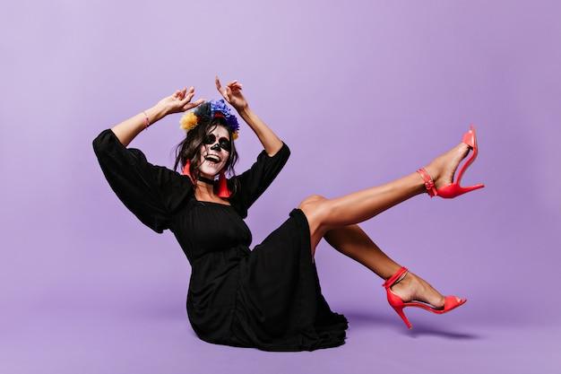 할로윈 얼굴 아트와 곱슬 갈색 머리는 바닥에 앉아있는 동안 노래합니다. 라일락 벽에 높은 영혼에 여자의 사진.