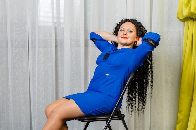 파란색에서 곱슬 갈색 머리 여자는 다시 던져 그녀의 머리와 함께 의자에 앉아있다. 가로 사진