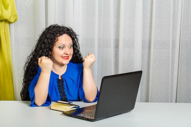 곱슬 갈색 머리 여자는 사무실 테이블에 앉아 영상 통신을 통해 감정적으로 의사 소통합니다. 가로 사진