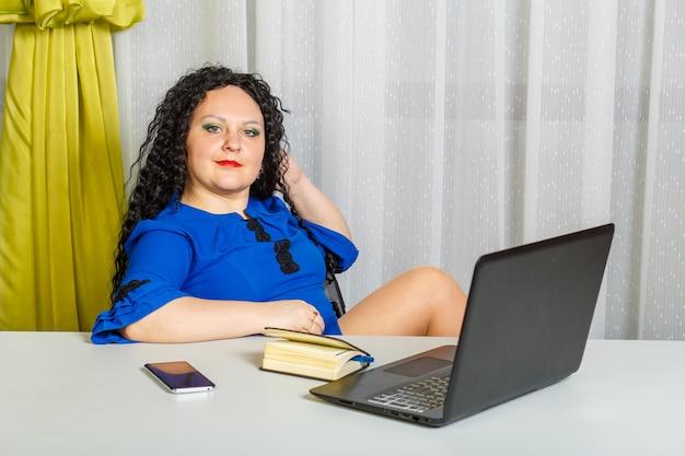 곱슬 갈색 머리 여자는 테이블에 그녀의 다리로 작업을 마친 후 쉬고 사무실에서 테이블에 앉아있다. 가로 사진